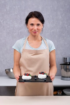 Portrait de femme chef pâtissier avec des gâteaux dans ses mains. gâteaux anna pavlova.