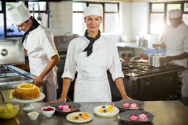 Portrait de femme chef présentant des assiettes à dessert
