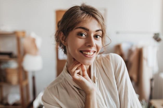 Portrait de femme en chemise beige posant dans un bureau lumineux