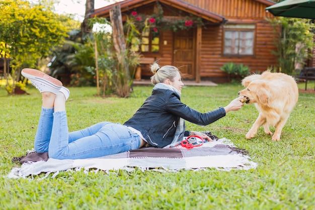 Portrait d'une femme avec un chien à l'extérieur. femme avec un animal de compagnie dans une maison de campagne.