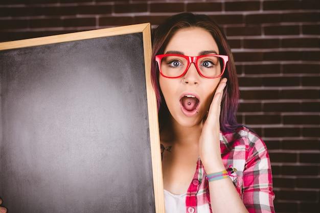Portrait de femme choquée tenant l'ardoise