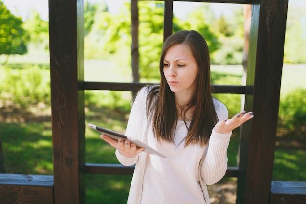Portrait d'une femme choquée triste et bouleversée portant des vêtements légers et décontractés. jolie fille tenant un ordinateur tablette, lisant de fausses nouvelles dans le parc de la ville dans la rue à l'extérieur sur la nature verdoyante du printemps. concept de mode de vie.
