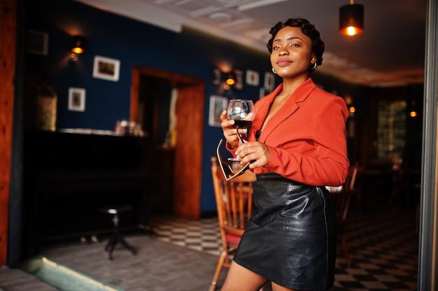Portrait de femme avec une coiffure rétro porte une veste orange au restaurant avec un verre de vin