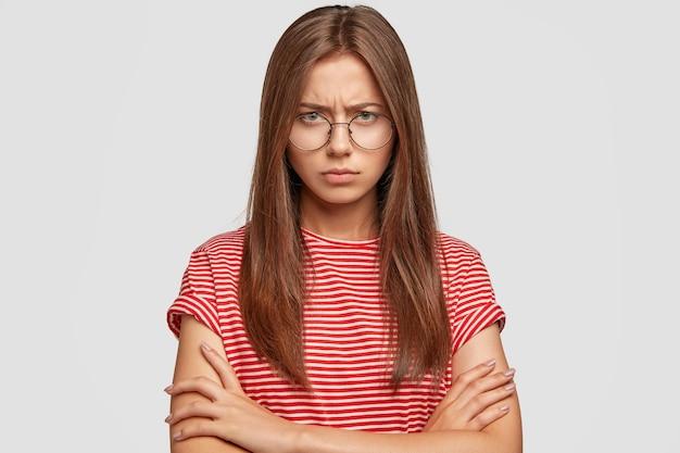 Portrait de femme en colère offensée se tient dans un geste insulté, a boudé le visage, garde les bras croisés