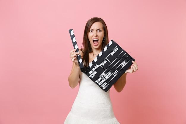 Portrait de femme en colère en robe blanche criant tenant un film noir classique faisant des clap