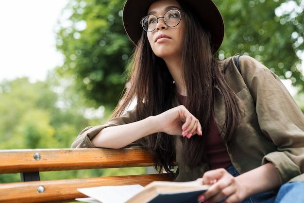 Portrait d'une femme concentrée avec de longs cheveux noirs portant un chapeau et des lunettes lisant un livre assis sur un banc dans un parc verdoyant