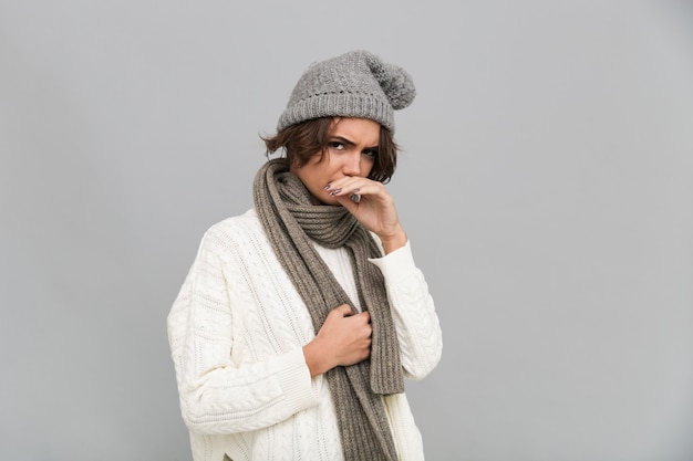 Portrait d'une femme congelée insatisfaite en écharpe et chapeau