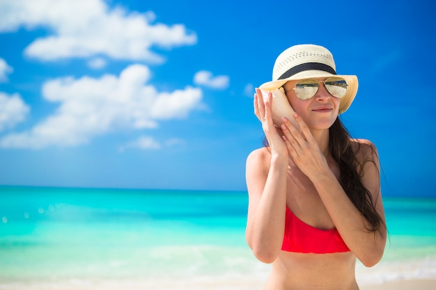 Portrait de femme avec coquillage dans les mains sur une plage tropicale