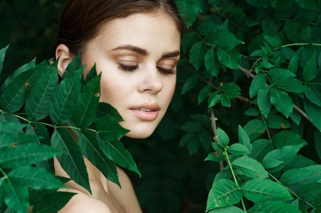 Portrait d'une femme cosmétologie nature feuilles vertes modèle glamour