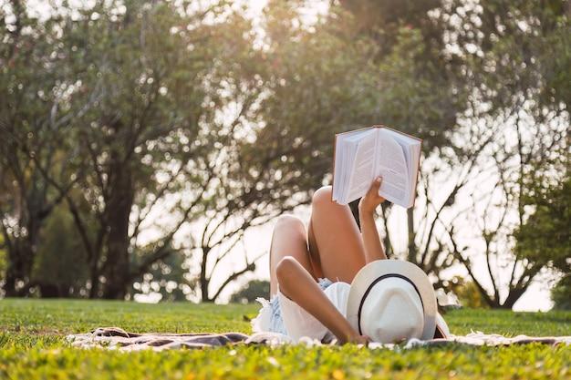 Portrait d'une femme couchée dans le parc en lisant un livre