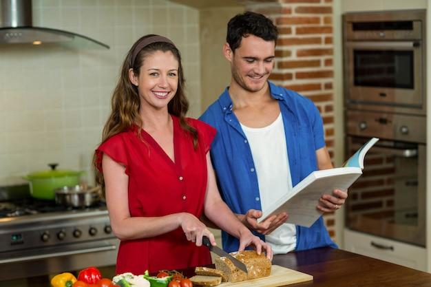 Portrait, femme, couper, miche pain, tandis que, homme, vérification, livre de recettes, cuisine, maison
