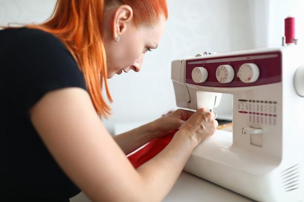 Portrait de femme couturière travaillant sur machine à coudre blanche