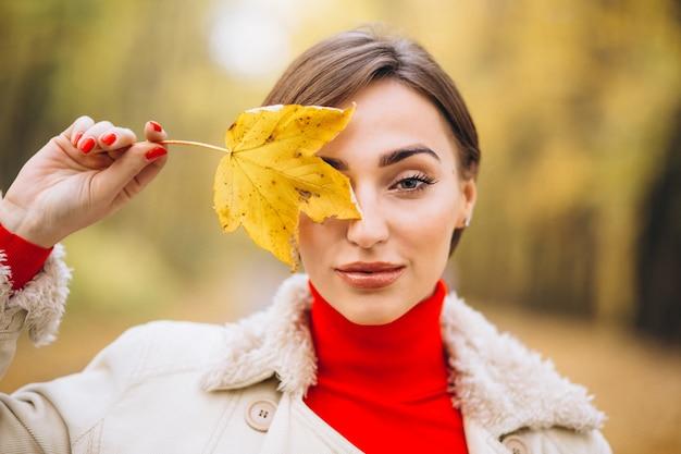 Portrait de femme couvrant la moitié du visage avec une feuille