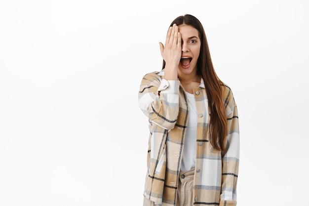 Portrait d'une femme couvrant la moitié de son visage et ayant l'air surpris par un autre, haletant impressionné et excité, vérifiant l'offre promotionnelle impressionnante, voir l'offre impressionnante dans la boutique, mur blanc