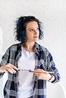 Portrait d'une femme créative artiste mettant des peintures à l'huile sur palette travaillant dans son studio