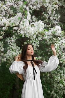 Portrait d'une femme dans les branches d'un pommier en fleurs. beau maquillage naturel