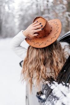Portrait d'une femme dans un chapeau dans la forêt d'hiver en voiture noire