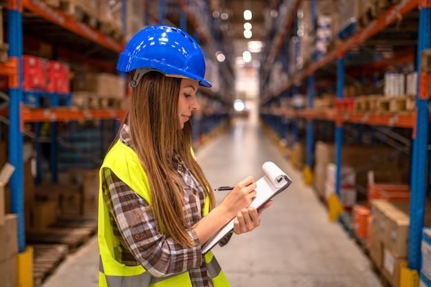 Portrait de femme dans l'entrepôt de distribution en prenant des notes
