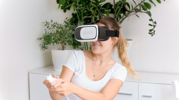 Portrait de femme dans des lunettes vr jouant à un jeu vidéo à 360 degrés et utilisant un joystick ou une télécommande.