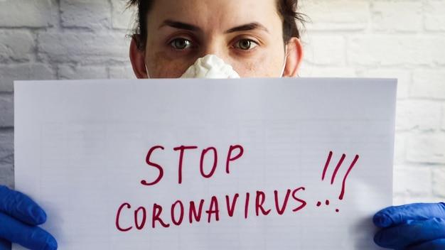 Portrait d'une femme dans un masque de protection qui montre la caméra en gros plan sur une feuille de papier blanche avec le texte stop coronavirus écrit au marqueur rouge. le concept de coronavirus de quarantaine dans le monde.
