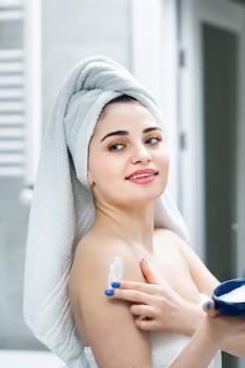 Portrait de femme dans la salle de bain appliquant une crème hydratante dans la salle de bain après la douche