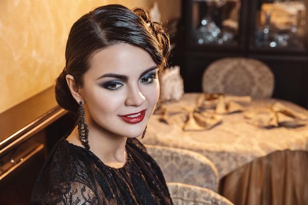 Portrait d'une femme dans un style rétro, maquillage lumineux, coiffure du soir.