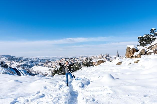 Portrait d'une femme dans une vallée de neige. vue de la ville enneigée de tolède en arrière-plan.