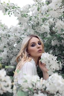 Portrait d'une femme dans un verger de pommiers en robe blanche. visage d'une fille en fleurs de pommier close up