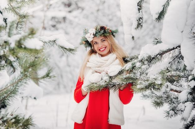 Portrait d'une femme dans une veste rouge dans une forêt d'hiver froid.