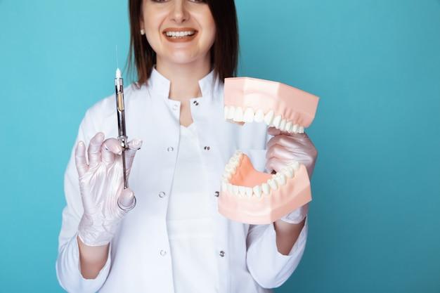 Portrait de femme dentiste avec fausse mâchoire et syrigne dentaire isolée.