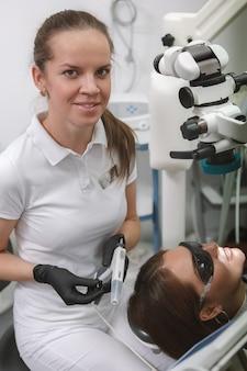 Portrait d'une femme dentiste joyeuse souriant à l'avant tout en travaillant