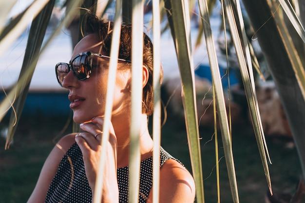 Portrait d'une femme derrière des feuilles de palmier