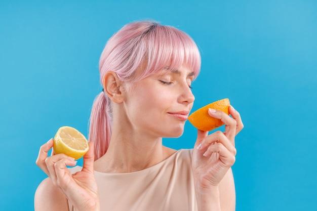 Portrait d'une femme détendue aux cheveux roses tenant la moitié d'orange fraîche et de citron le sentant avec