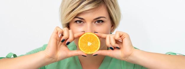 Portrait de femme diététiste tenant et montrant une tranche d'orange
