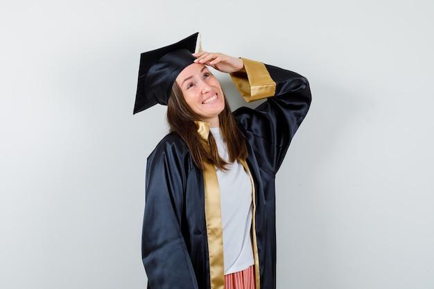 Portrait de femme diplômée en gardant la main sur la tête en tenue académique et à la vue de face heureuse
