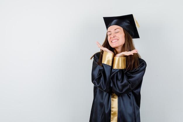 Portrait de femme diplômée en gardant les mains sous le menton en robe académique et à la vue de face heureuse