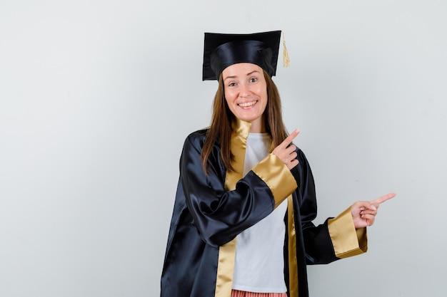 Portrait de femme diplômée pointant sur le coin supérieur droit en tenue académique et à la vue de face heureuse