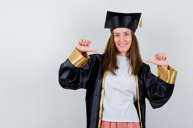Portrait de femme diplômée pointant sur elle-même avec les pouces dans des vêtements décontractés, uniforme et à la vue de face confiante