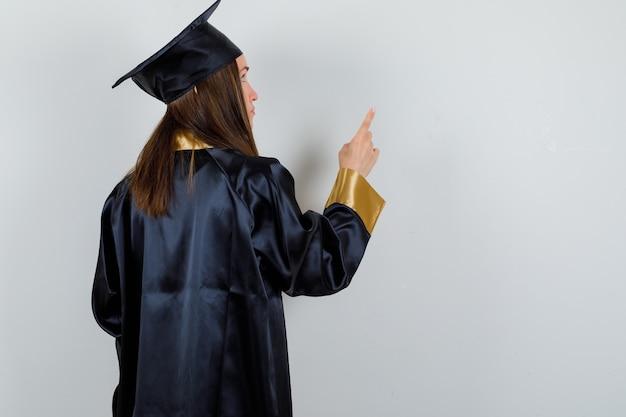 Portrait de femme diplômée pointant vers le haut en uniforme et à la vue arrière focalisée