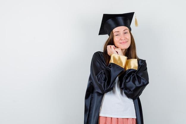Portrait de femme diplômée posant avec les mains jointes dans des vêtements décontractés, uniforme et à la gracieuse vue de face