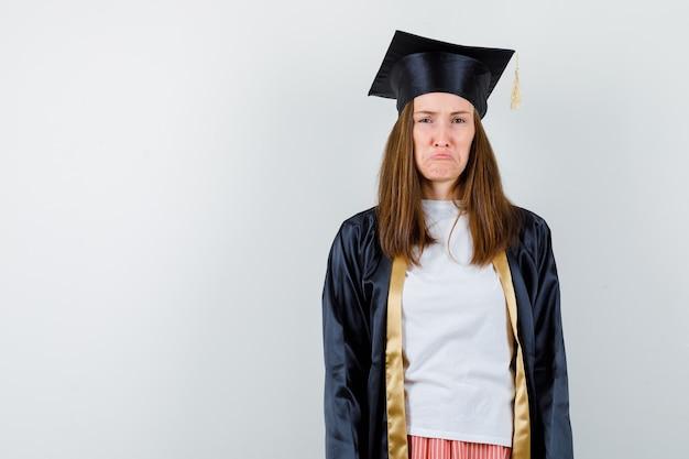 Portrait de femme diplômée regardant la caméra tout en fronçant les sourcils, lèvres courbes dans des vêtements décontractés, uniforme et à la vue de face offensée
