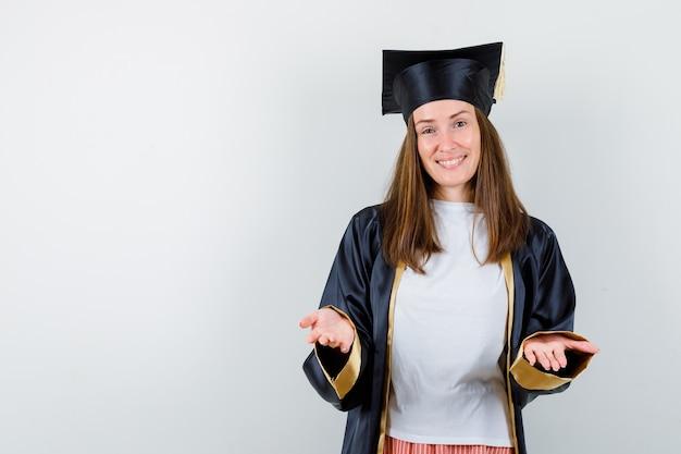 Portrait de femme diplômée répandre les mains à la caméra dans des vêtements décontractés, uniforme et à la joyeuse vue de face
