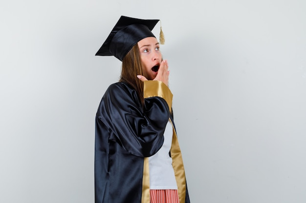 Portrait de femme diplômée tenant la main sur la bouche ouverte tout en bâillant dans des vêtements décontractés, uniforme et à la vue de face de rêve
