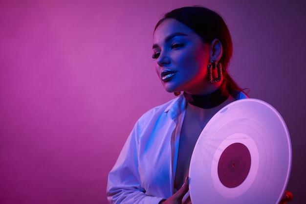 Portrait de femme disco tenant un vinyle rétro avec musique des années 80 sur fond clair néon.