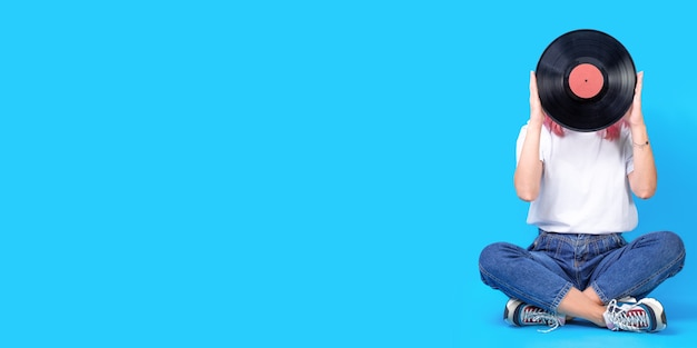 Portrait de femme dj avec disque vinyle sur fond bleu. photo rétro de femme avec disque vinyle. bannière large