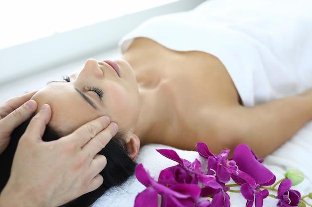 Portrait de femme dont le maître fait un massage du visage par acupression.
