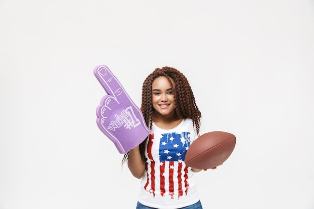 Portrait d'une femme drôle tenant un gant de fan numéro un et un ballon de rugby tout en se tenant isolé contre un mur blanc