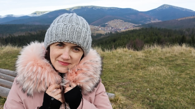 Portrait d'une femme avec du rouge à lèvres rouge sur fond de montagnes.