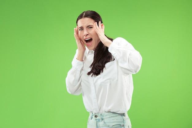 Portrait de la femme effrayée sur vert