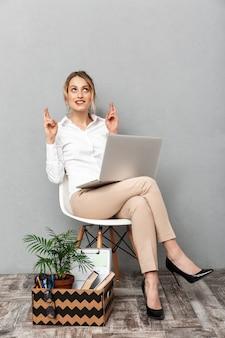Portrait de femme élégante à l'aide d'un ordinateur portable assis dans une chaise avec des choses de bureau, isolé